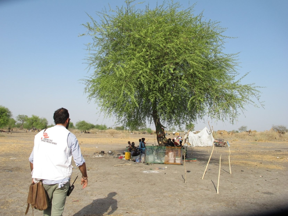 A MSF staffer visits a family living under a tree in Noon.