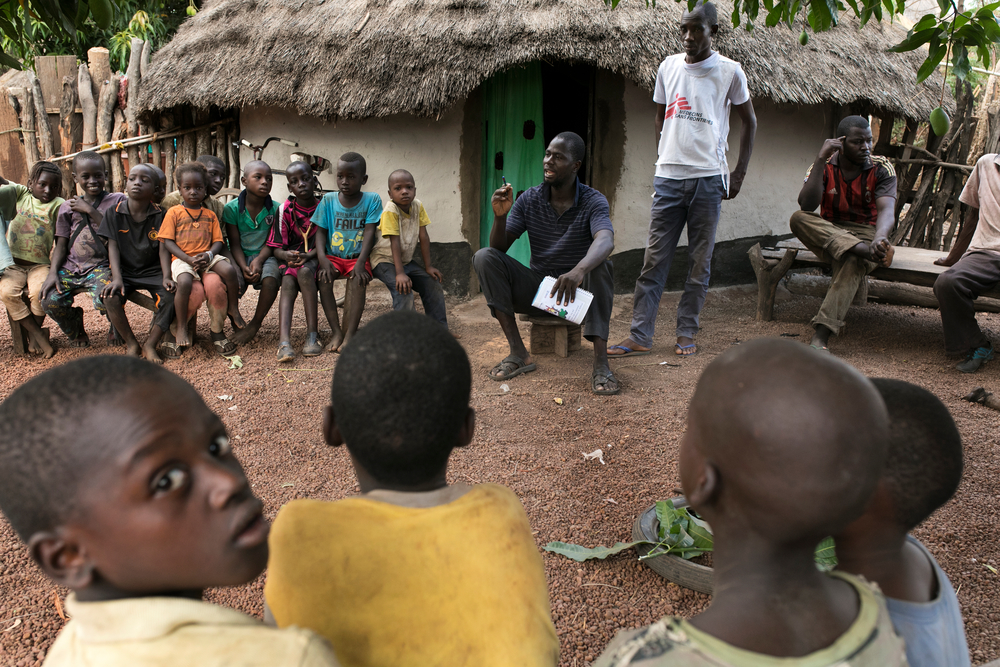 Sekouba Souare, a community health worker trained by MSF, reaches out to villagers in Kakidi, Guinea.