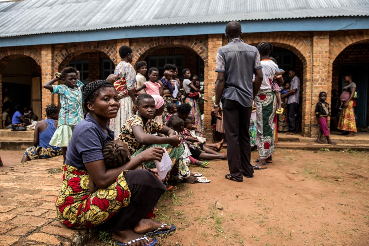Mothers and children wait to be treated for malnutrition outside the Mayi Munene health center in DRC's Kasai region.