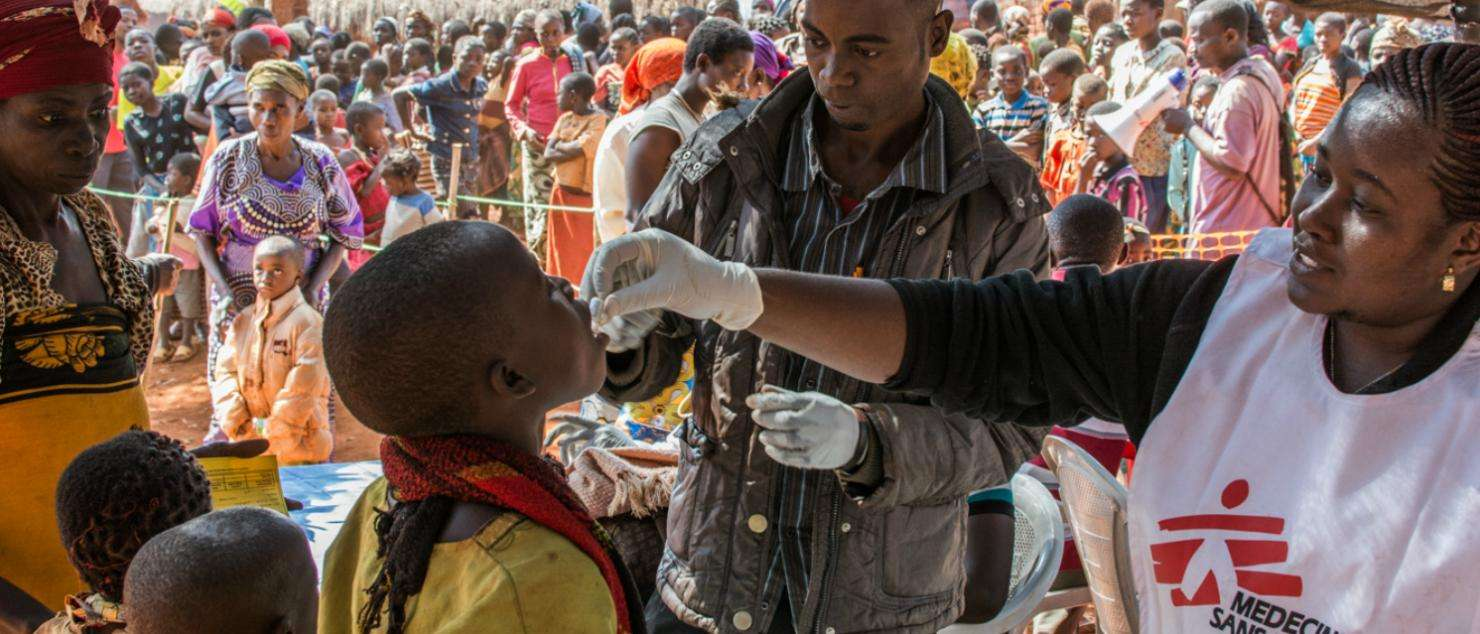 MSF staff administrate an oral vaccine to a boy at a refugee camp