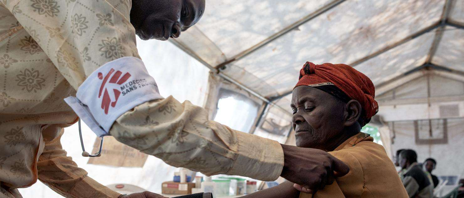 An MSF mobile clinic medical staff consults with a Burundian refugee.