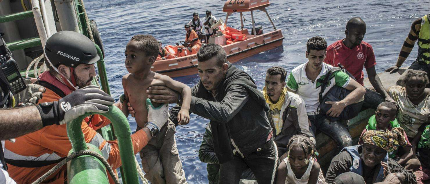 A young child is lifted from a boat containing approximately 650 refugees