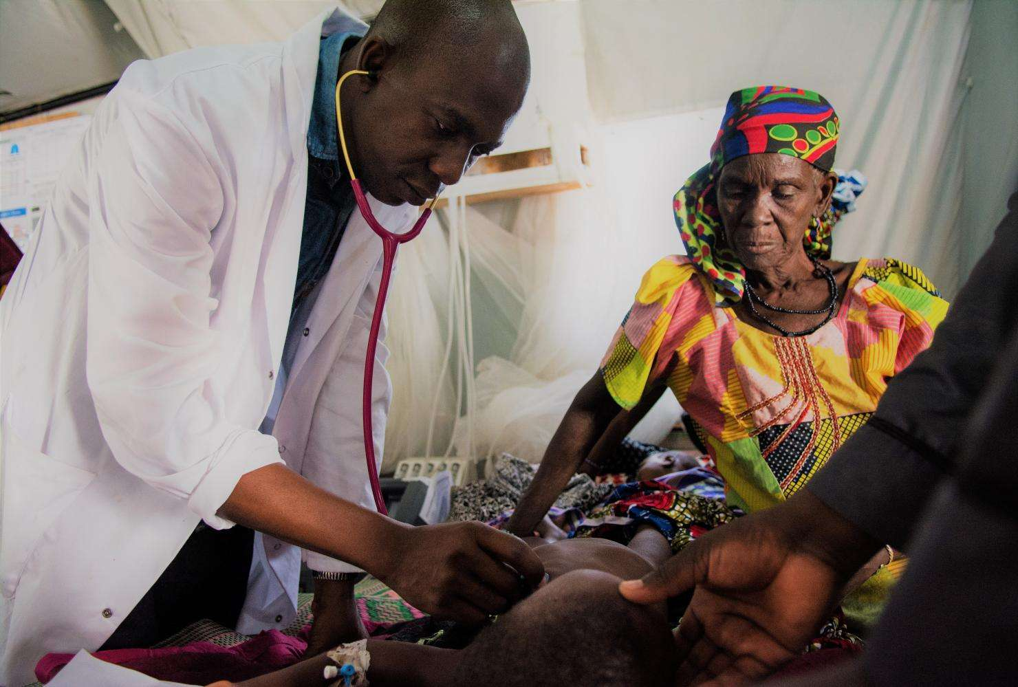 A physician providing care to a sick child at MSF's temporary hospital at Dungass, in the Magaria area