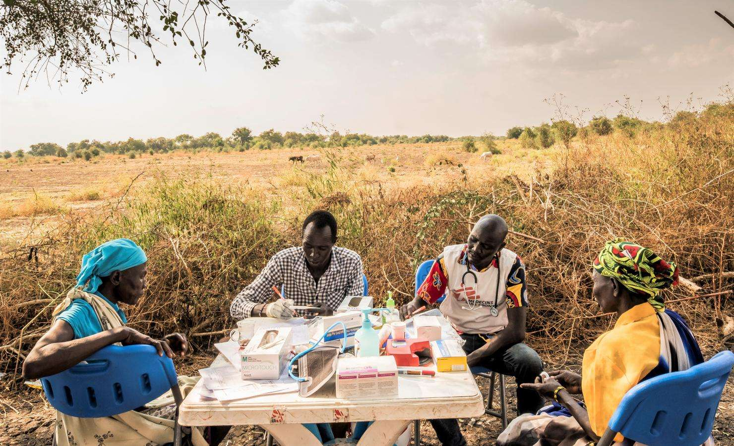 In the shade of a tree, mobile medical staff provide health consultations. Once per week, MSF sets up its medical clinic under trees in the village of Kier, on the banks of the Pibor River.