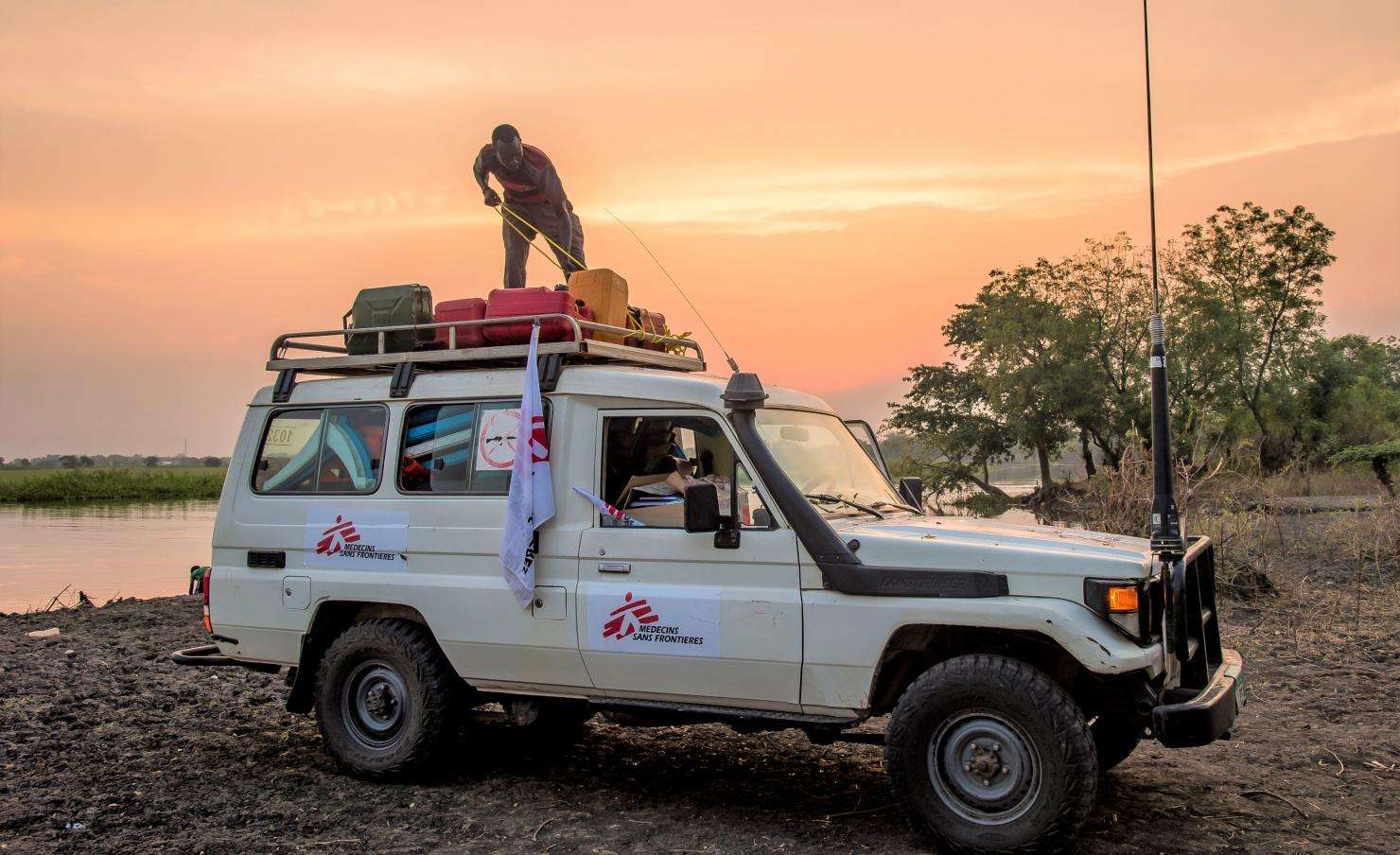In a remote area of South Sudan, an MSF logistician, attaches to the roof of a 4x4, the equipment that a mobile clinic team has just brought back after a day of mobile boat clinics.