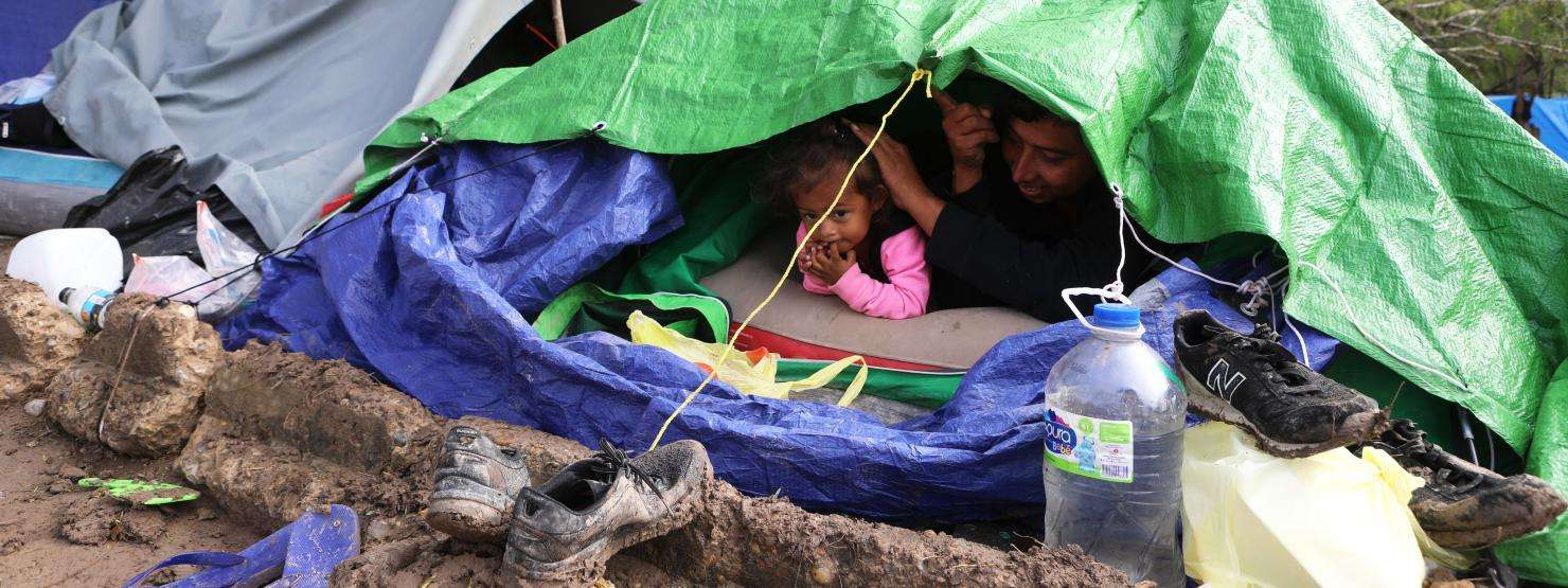 A family peeks out of their tent on a very cold day at an encampment near the international bridge connecting Matamoros, Mexico, with Brownsville, Texas.