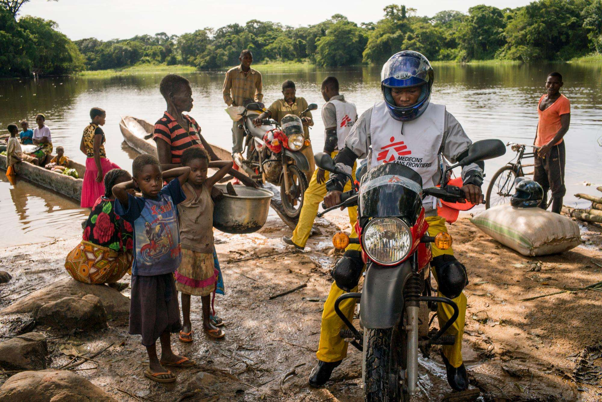 MSF team members travel by motorbike during a 2016 measles vaccination campaign.