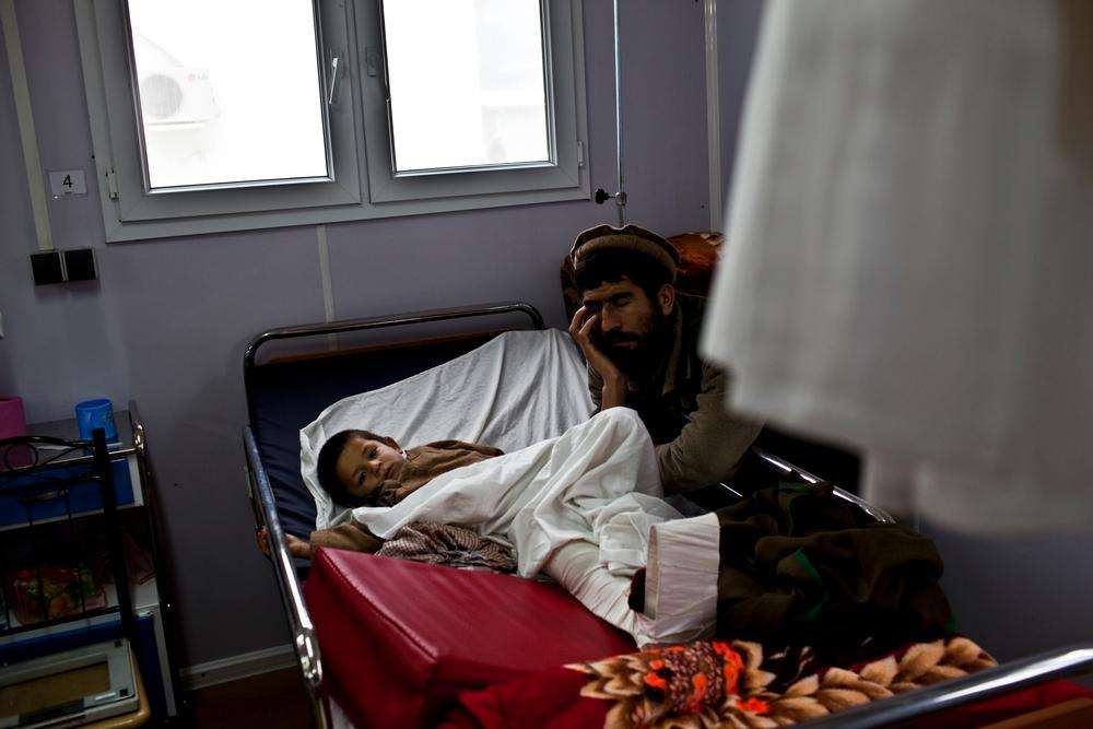 A man naps next to his son recovering in the MSF trauma hospital in Kunduz, northern Afghanistan, November 30, 2011