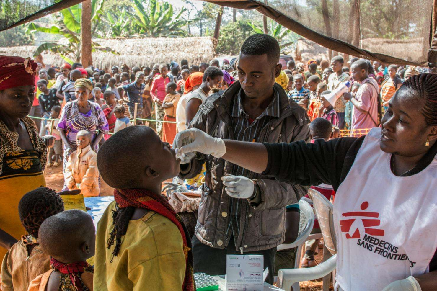 MSF Staff administrate oral vaccine to a boy in a refugee camp