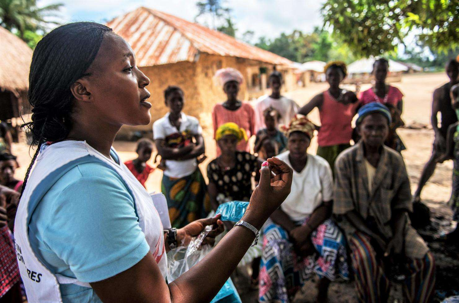Health promoter, Emma Kamara, talks to villagers about health issues during a MSF outreach mission to treat survivors of Ebola.