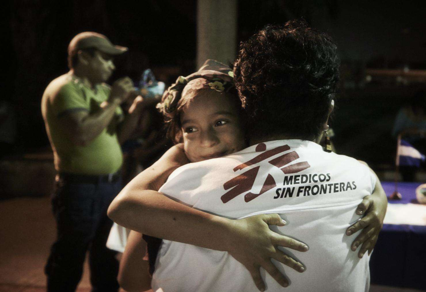 An MSF social worker hugs a migrant girl.