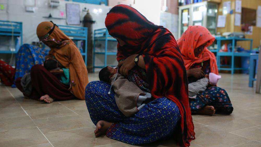 Khan bibi along with other new mothers learns to feed her newborn baby at the nursery in DHQ hospital, Dera Murad Jamali in Balochistan province, Pakistan