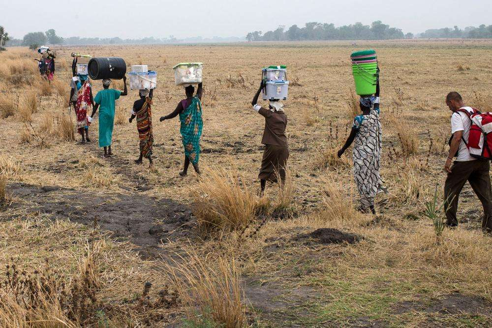 Women carry Medecins Sans Frontieres (MSF) equipment as the medical team moves from one location to the other to be flown out of the area after having finished their work at various MSF outdoor support clinics, close to Thaker, Leer County, South Sudan, March 23, 2017.