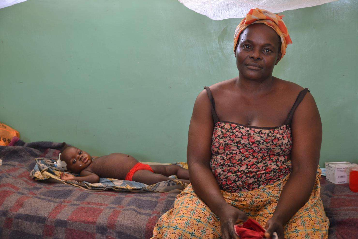 A woman sits on a bed with her child, a measles patient