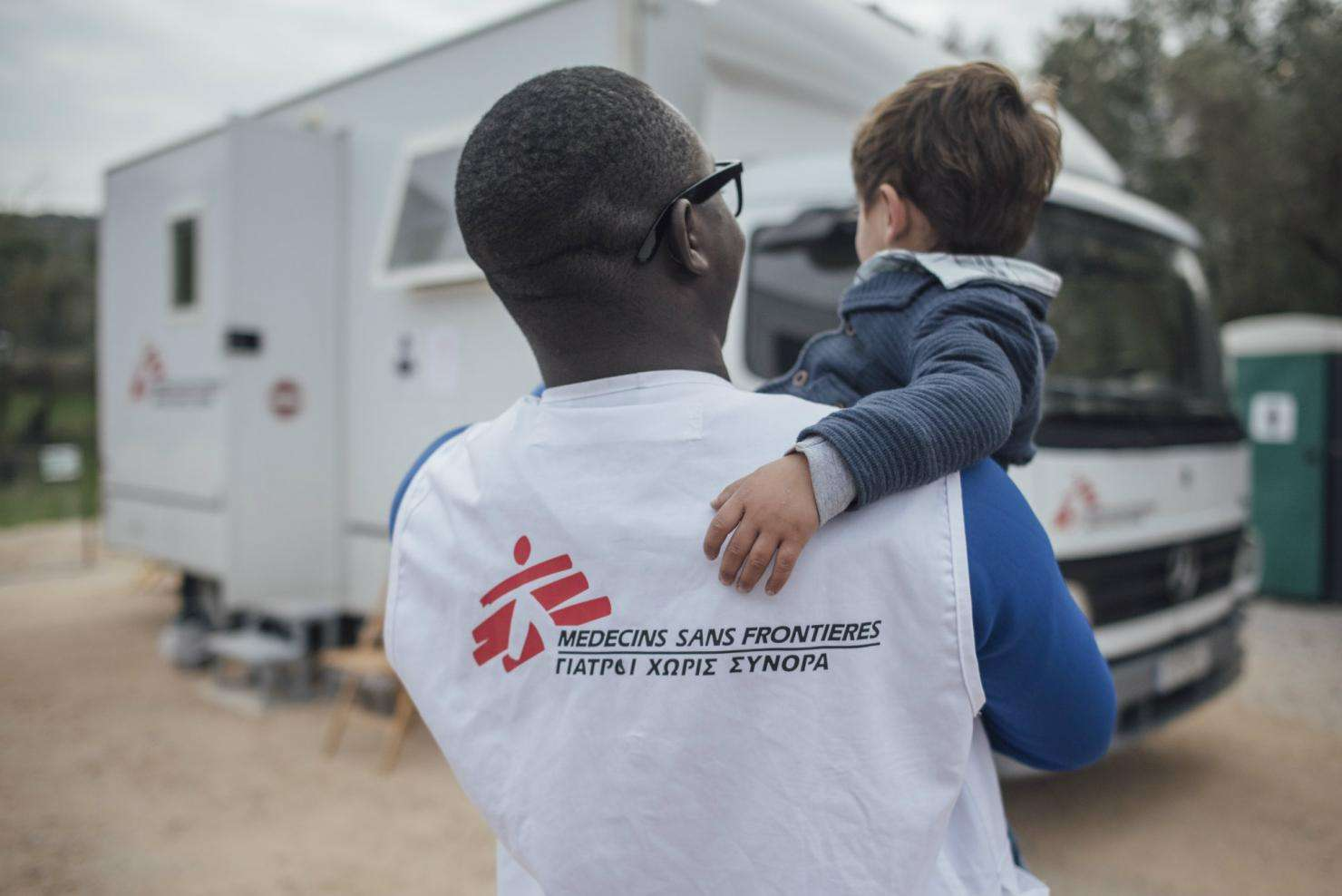 An MSF doctors carries a young patient to MSF's mobile clinic in Moria camp, Greece.