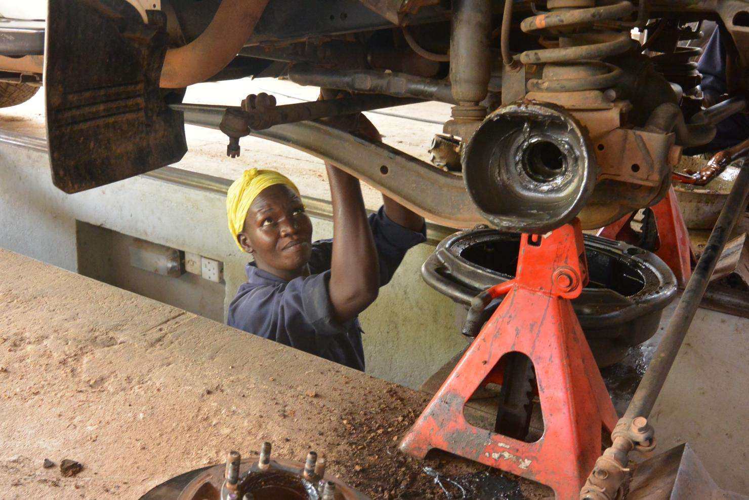 Poni Betty works on the underside of a vehicle at the MSF workshop in Juba, South Sudan.