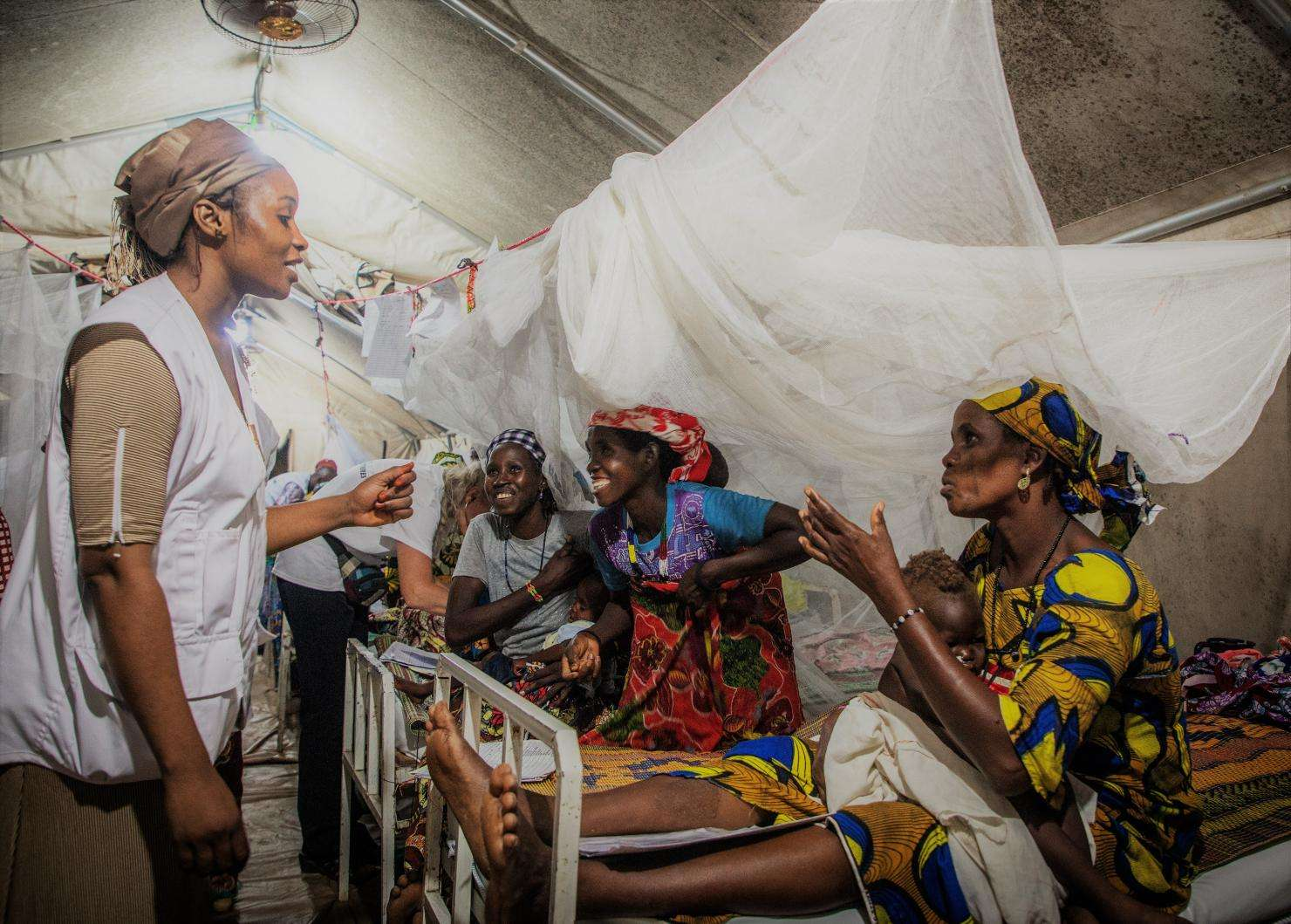A MSF nurse talking to a mother in the phase 2 tent during the evening visit