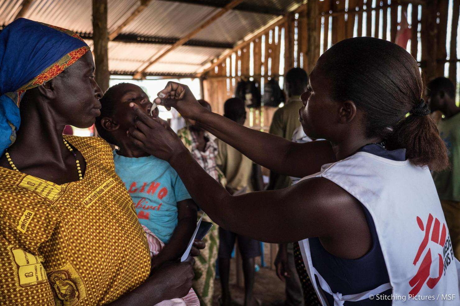 An MSF staff member administers the oral cholera vaccine to a child in Kyangwali, Uganda.