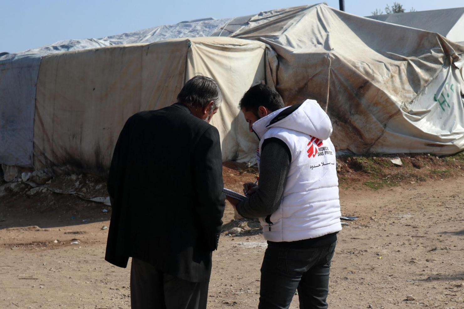 An MSF health worker talks with a Syrian man in Qadimoon camp.