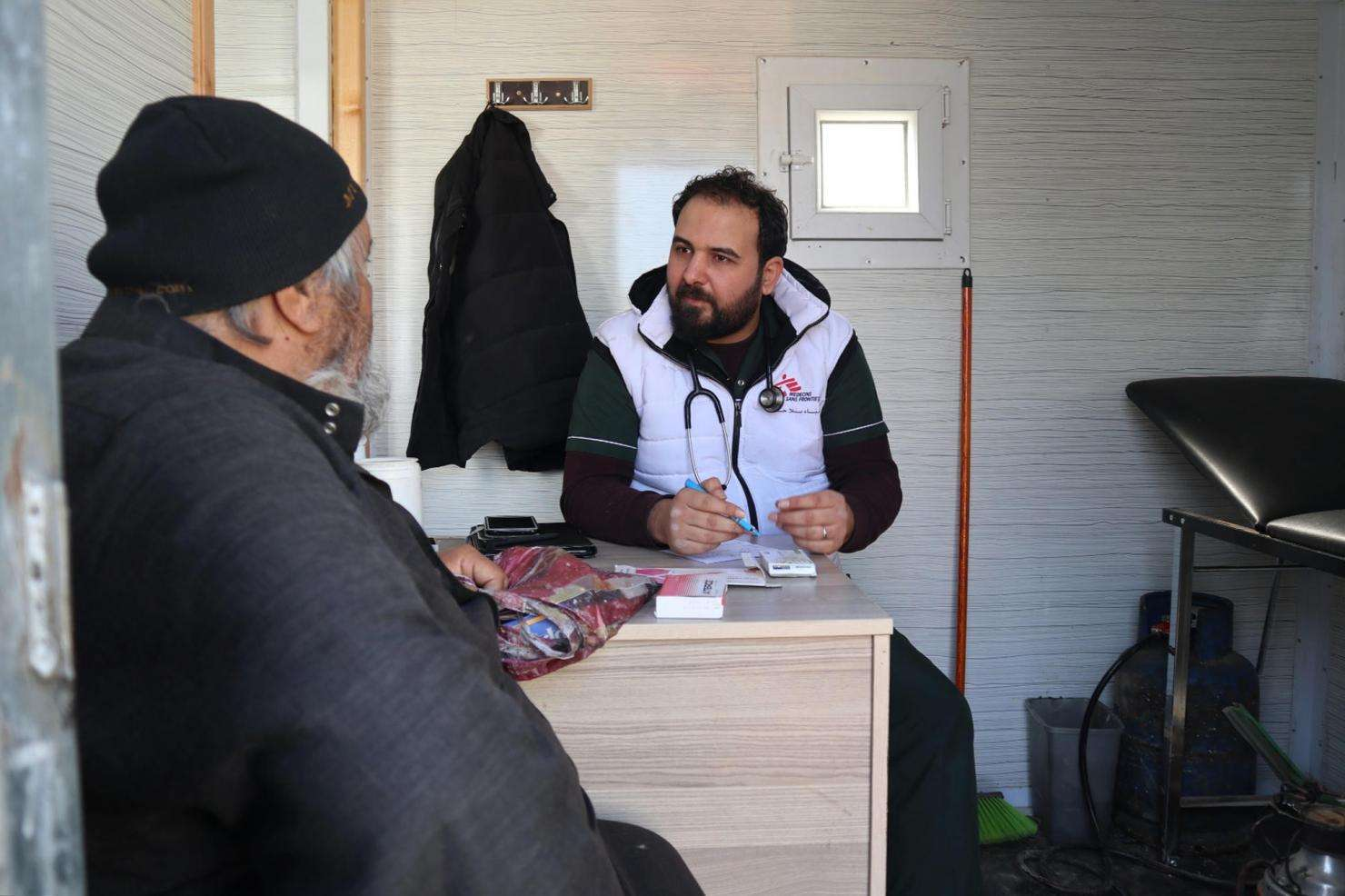 A patient talks with a doctor at MSF's mobile clinic in Qadimoon camp, Northwest Syria.