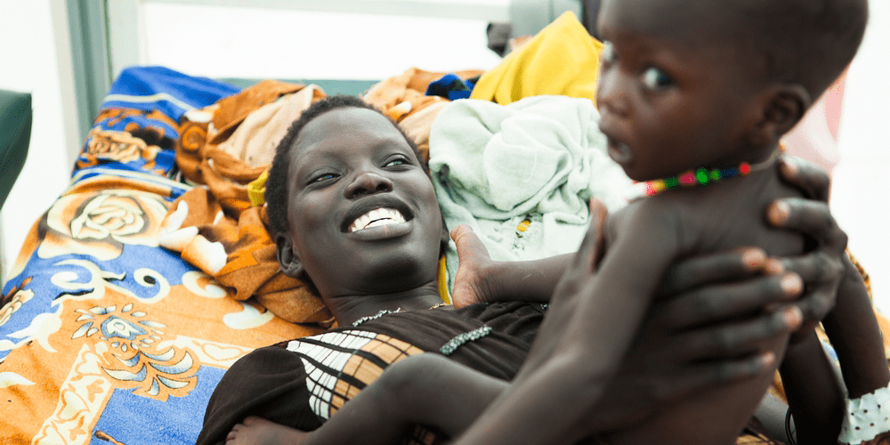 A mother holding her baby in Bentiu, South Sudan