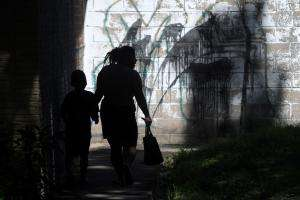 A woman and her son walk past graffiti referencing the M13 gang in Las Margaritas, Soyapango, El Salvador.