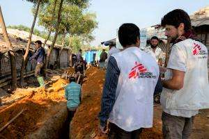 Paolo and Chandon, MSF water and sanitation logisticians, in front of the excavations for the sediment of pipes carrying water in camp 1 in Kutupalong and Balukali areas.