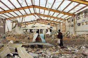 Yemenis survey the damage caused by a Saudi-led airstrike on an MSF-supported cholera treatment center in Yemen's Abs region in June. No staff or patients were killed or injured in the attack.