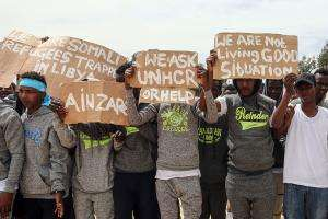 Migrants hold placards during United Nations Secretary-General Antonio Guterres (not pictured) visit to Ain Zara detention centre for migrants in the Libyan capital Tripoli on April 4, 2019.