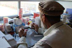 Dr Wardak Abdul Qayoum observes a culture plate to find an interesting bacterial strain in the laboratory in Boost Hospital, Lashkar Gah, Helmand, Afghanistan.