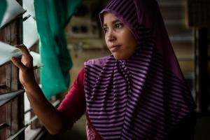 A Rohingya refugee looks out of her window in Malaysia