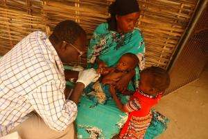 A child is examined by a nurse in the small village of Sortoni, Darfur.