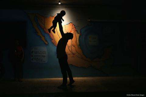 A Honduran man holds a young child at La 72 shelter in Mexico