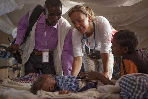 Dr Josine Blanksma examines a child in the therapeutic feeding center in Baraka Hospital. She is assisted with interpreting by Enala Maonyesho, left.