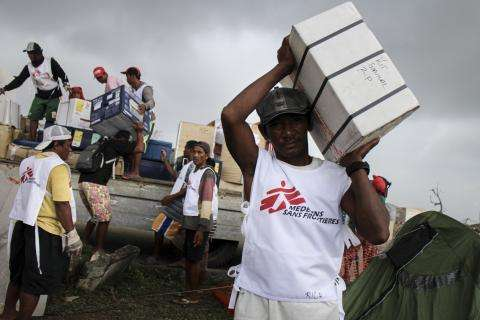 MSF logistician and daily workers unload a truck with humanitarian supplies