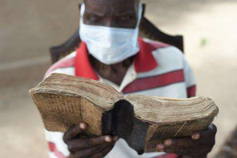 Obert, 86, reads his bible in Zimbabwe