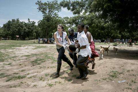 An MSF nurse leads an evacuation of a woman with pregnancy complications.