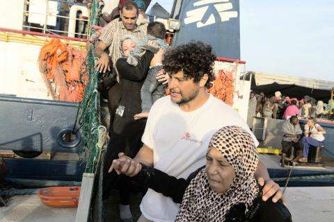 MSF cultural mediator helps older woman disembark from the MSF search and rescue vessel, Dignity I