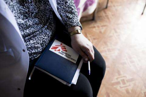 A woman holds a book in her lap