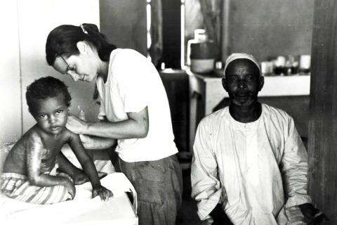 A MSF volunteer examines an infant in Sudan.
