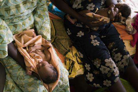 Twins are held on the bed in the maternity ward of the MSF hospital in Aweil, South Sudan.