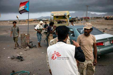 MSF staff speaking with armed men at a check point