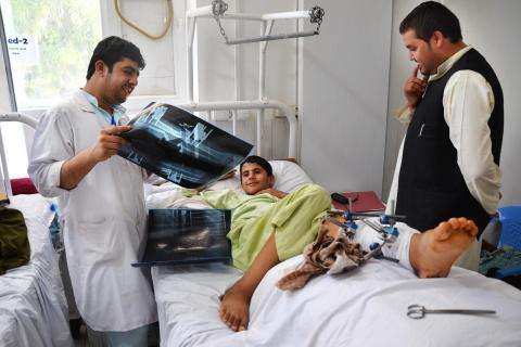 MSF physiotherapist looks over x-rays with a 14-year old patient at Boost hospital in Lashka Ghar, Helmand province, Afghanistan.