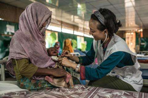 A health worker tends to a young patient at the MSF hospital in Goyalmara, Cox's Bazar, Bangladesh.